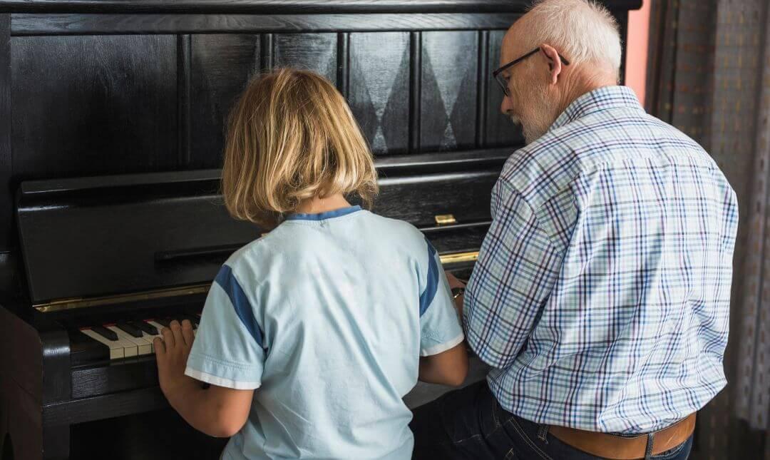 Barn och farfoeraeldrar spelar piano